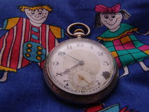 Old pocket watch on juvenile textile. An old pocket watch, with the number four missing, sits atop a textile print featuring cartoon style illustrations of a Royalty Free Stock Photo