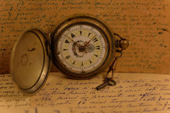 Old pocket watch with key Stock Photo