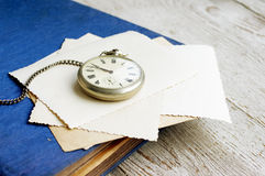 Old pocket watch, old photo album and old empty photographs Royalty Free Stock Photos