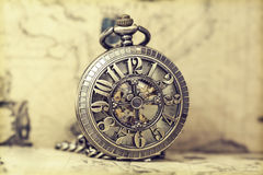 Old pocket watch over vintage map. Vintage watch on antique map. Retro still life Royalty Free Stock Image
