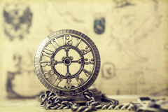 Old pocket watch over vintage map. Vintage watch on antique map. Retro still life Stock Image