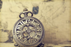 Old pocket watch over vintage map Stock Photos