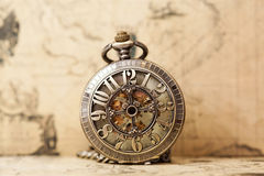 Old pocket watch over vintage map. Vintage watch on antique map. Retro still life Royalty Free Stock Photos