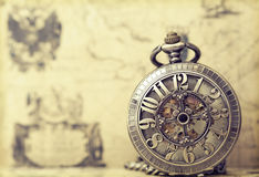 Old pocket watch over vintage map. Vintage watch on antique map. Retro still life Stock Photo