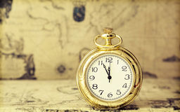 Old pocket watch over vintage map. Vintage watch on antique map. Retro still life Royalty Free Stock Photo