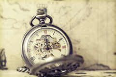 Old pocket watch over vintage map. Vintage watch on antique map. Retro still life Royalty Free Stock Images