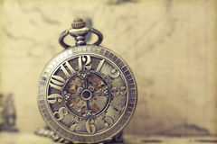 Old pocket watch over vintage map. Vintage watch on antique map. Retro still life Stock Photos