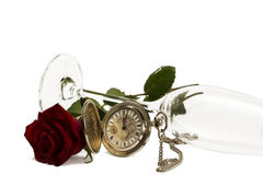 Old pocket watch with a red wet rose under a lying. Champagne glass on white background Stock Photography