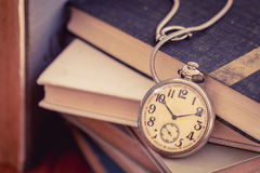 Old pocket watch on stack of books Stock Photo