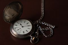 Old pocket watch on top of a wooden box Royalty Free Stock Photo