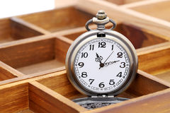 Old pocket watch. In old wooden container Stock Image