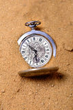 Old pocketwatch laying on the sand Stock Images