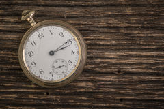 Old Pocketwatch Over Rough Wood Background. An old pocket watch on a rough worn wood background Royalty Free Stock Photography