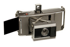 Old Polaroid camera. An early 1960's era Polaroid camera spits out a Polaroid print.  The print is a mask that allows you to place any image within the print you Stock Image