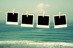 Old polaroid photo frames hanging on a rope with beach background Stock Image