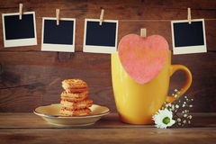 Old polaroid photo frames hanging on a rope with coffee cup and cookies over wooden background Royalty Free Stock Images
