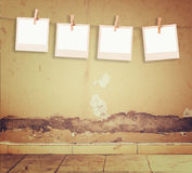 Old polaroid photo frames hanging on a rope over textured grunge wall and floor pattern Royalty Free Stock Images