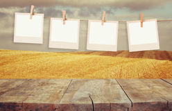 Old polaroid photo frames hanging on a rope with vintage wooden board table in front of wheat field landscape.  royalty free stock photography