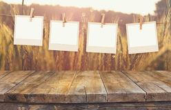 Old polaroid photo frames hanging on a rope with vintage wooden board table in front of wheat field landscape Stock Images