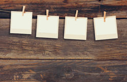 Old polaroid photo frames hanging on a rope with wooden background Stock Images