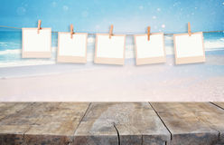 Old polaroid photo frames hnaging on a rope with beach background Royalty Free Stock Image