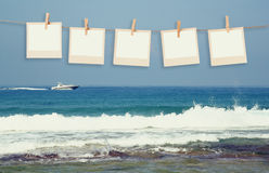 Old polaroid photo frames hnaging on a rope with beach background Royalty Free Stock Photo
