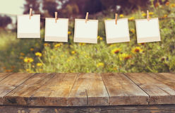 Old polaroid photo frames hnaging on a rope with vintage wooden board table in front of summer flowers field bloom landscape.  royalty free stock photo