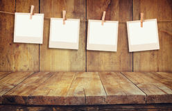 Old polaroid photo frames hnaging on a rope with wooden background Royalty Free Stock Photos