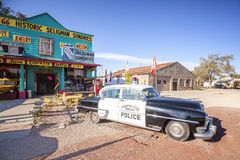 Old police car in front of historic Sundries Building. Seligman, USA - September 10, 2015: Old police car in front of historic Sundries Building. The town was Royalty Free Stock Images