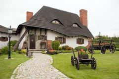 Old polish house. Old-fashioned polish house with farm carriage flowerpot stock photo