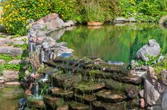 Old pond in garden. Old pond on a summer day in the garden Stock Image