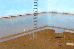 Old pool. Old abandoned pool with rusty ladder Stock Photos