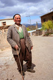 An old poor man. Standing in front of his village Royalty Free Stock Photo