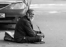 An old poor sad man begging on a sidewalk near the Bucharest city center Royalty Free Stock Photography