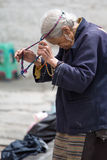 Old and poor Tibetan woman during her religious ceremony Royalty Free Stock Photography