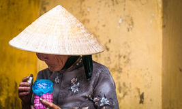 Old poor woman in conical hat holding pink jar. Royalty Free Stock Photos