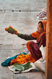 Old poor woman sells garlands of flowers at the temple Stock Photo