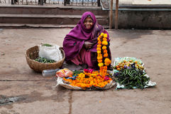 Old poor woman sells garlands of flowers at the temple Stock Photos