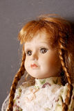 Old porcelain doll. On gray background stock image