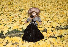 old porcelain doll on blur ginkgo leave background Royalty Free Stock Photos