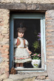 Old porcelain doll at the window Stock Photography
