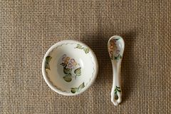 Old porcelain plate with spoon on tablecloth linen stock photography
