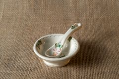 Old porcelain plate with spoon on tablecloth linen Royalty Free Stock Images