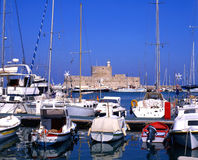 Old Port. Boats moored in harbour of Rhodes, greece, with old fort in background stock photo