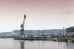 Old port crane and harbor structures. In Sevastopol Bay Stock Image