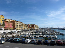 Old port at Nice, France. Colored buildings next to the old port with many boats and cars along at Nice, France, by beautiful weather Stock Photos