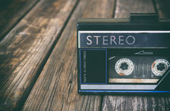Old portable cassette player on a wooden background. image is instagram style filtered.  royalty free stock photography