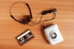 Old portable cassette tape player and headphones on wooden. Floor stock photo