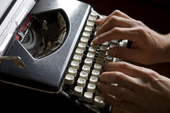 Old portable typewriter. Man typing on an old portable typewriter stock photo