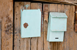Old post boxes on the wooden wall of slum house in Stock Photography